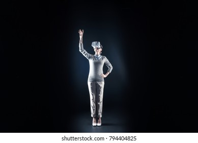 Smart technologies. Delighted joyful positive woman smiling and holding her hand up while standing against black background