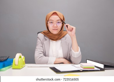 Smart thinking.Business concept.A young business woman wearing hijab holding a pen with smart decision action with artificial grain effect.Business and financial.