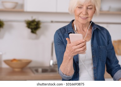 Smart user. Selective focus of a smartphone in hands of a nice senior woman using it while listening to music