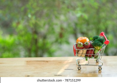 Smart vegetarian shopping for green healthy food and good heart concept. Shopping trolley full of vegetables, fruits, stethoscope, heart, medicines on brown table over blurred green background