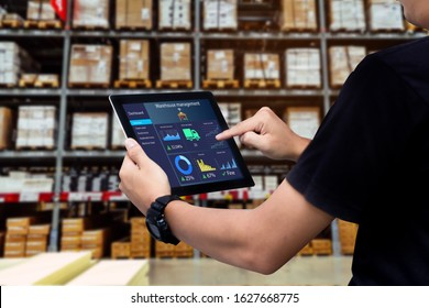 Smart warehouse management system.Worker hands holding tablet on blurred warehouse as background
