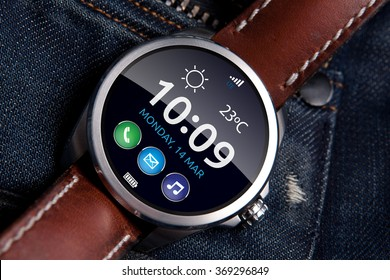 Smart watch concept on matte and polished metal case with brown leather strap on blue jeans background, display turned on