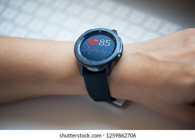Smart watch at woman's hand checking heart rate at the office