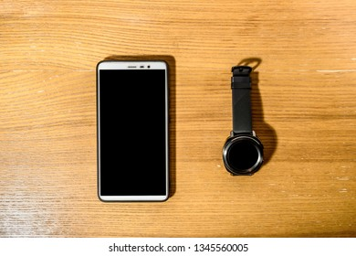 smart watch and smartphone lying on a wooden surface