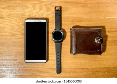 smart watch ,smartphone and wallet lie on the wooden table