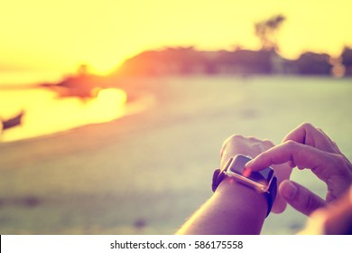 Smart watch woman using smartwatch touching button and touchscreen on active sports activity or morning jogging during beach sunrise or sunset.
