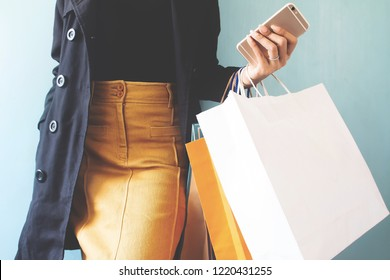 Smart woman in black overcoat with mobile phone and shopping bags. Shopping concept, Black Friday