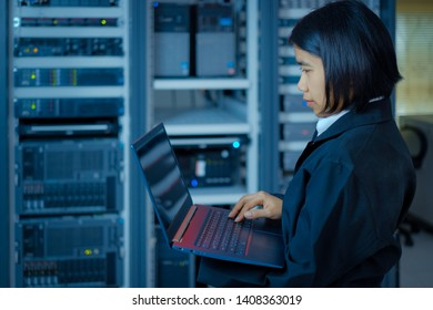 Smart woman or female technician or Network administrator working or checking data on a laptop in a data center room.