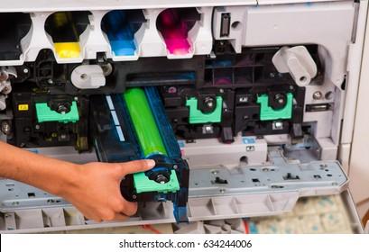 Smart woman fixing a photocopier during maintenance