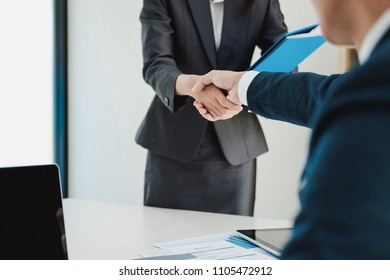Smart woman having a successful job interview, the examiner is shaking her hand