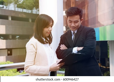 Smart woman and man in suit are standing outside the office.