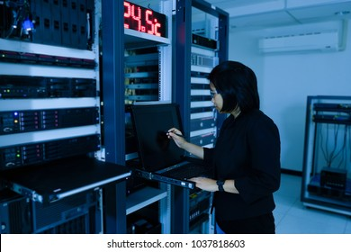 Smart woman manager in high technology concept. woman administrator in a technology data center room and black copy space on monitor