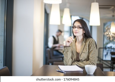 smart woman writing in a cafe