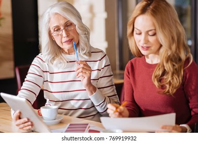 Smart women. Clever attentive senior woman sitting at the table and touching her lips with a pen while looking at the screen of a modern tablet with a young responsible designer sitting by her side