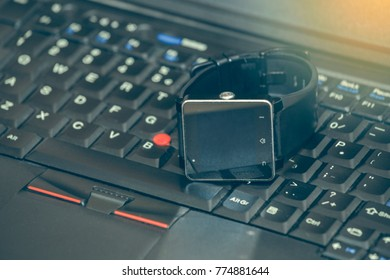 Smart wrist watch laying on a laptop keyboard. Abstract: always stay connected to internet and media.