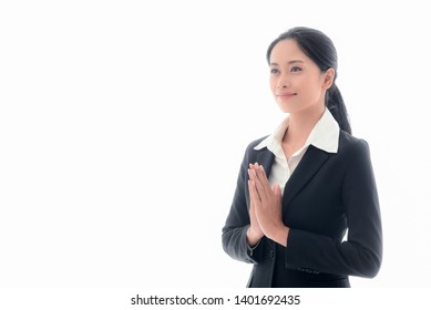 A smart and young Asian businesswoman in a suit. Being greeted by the Thai style with respect to or called ''Sawasdee'' with a smile, friendly and positive attitude on white background, receptionist