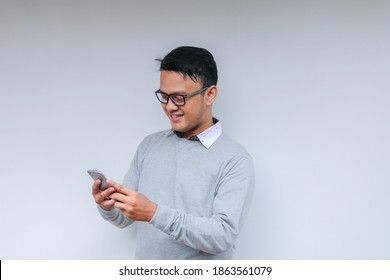 Smart Young asian man is happy and smiling when using smartphone in studio background