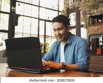 Smart young Asian man working with laptop during drinking coffee in working space.