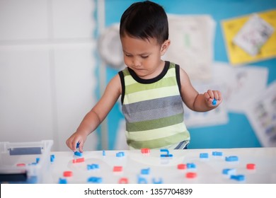 A smart young boy manipulating alphabet letters to form words in kindergarten room.