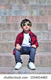Smart Young Boy Sitting in Sun on Stairs
