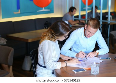 Smart young business men one woman suits sitting on table documents, graphics, technology,  Leaf catalog pages. Team entrepreneurs negotiate, discuss issues, solve problems, agree, talk