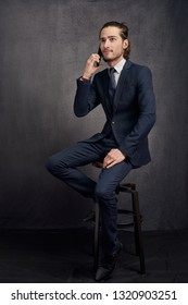 Smart young businessman in a stylish suit and tie sitting on a stool using a mobile phone listening to the call with a serious expression over dark grey studio background