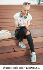 Smart young college student, urban woman, writing down some notes in her notebook, sitting outdoors on a beautiful sunny day