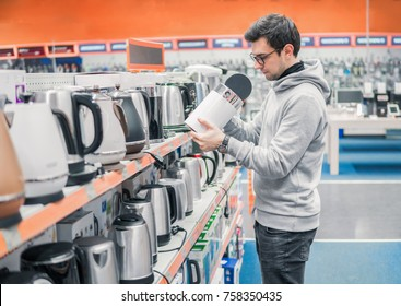 Smart young customer chooses a kettle in supermarket mall, at home electronics department, difficult decision. Various choice