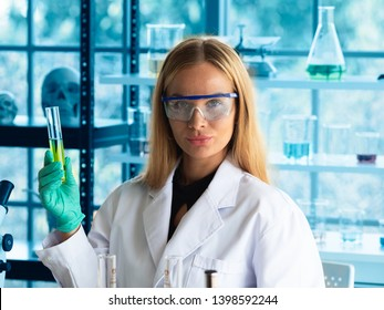 Smart young lady scientist shows glass tube with green liquid inside in the laboratory