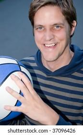 Smart young man holding basketball