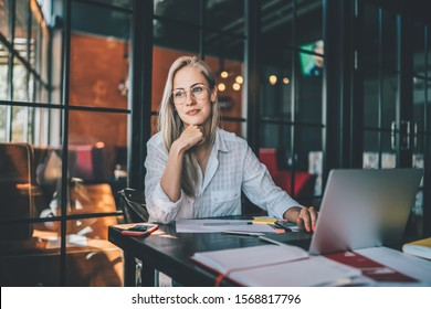 Smart young woman in casual clothes and glasses looking away and thinking while browsing laptop and doing freelance job in cafe