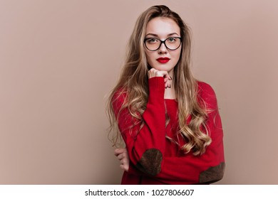 Smart young woman dressed glasses and red pullover with long hair and red lips poses on beige background with serious emotions. Indoor portrait of cheerful young woman smiling to camera.