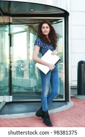 Smart young woman leaving an office building through revolving glass doors