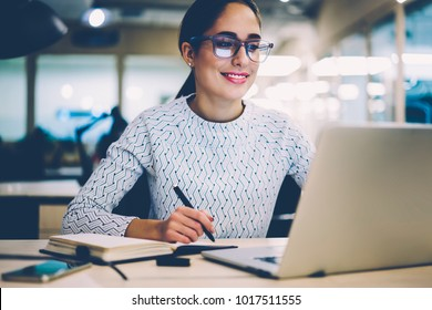 Smart young woman satisfied with learning language during online courses using netbook, smiling female student doing homework task in college library searching information via laptop computer