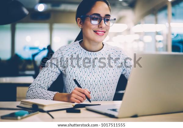 Intelligente junge Frau zufrieden mit dem Erlernen von Sprache in Online-Kursen mit Netbook, lächelnd weibliche Studentin, die Hausaufgaben in der College-Bibliothek Suche Informationen über Laptop-Computer