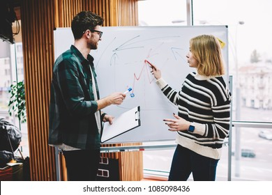 Smart young woman writing plan scheme on flipchart during training session conducting by successful male coach in university.Professional teacher checking graphic drawn on board by hipster student
