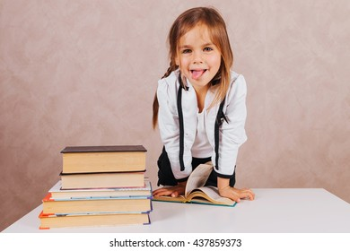 Smartest smart and beautiful little schoolgirl in school uniform with textbooks at school