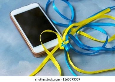 Smartfon and Xing yellow ribbons on a table. White gadget on a blue background. Colors of national flag