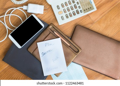 Smarthphone near paper list,pencil, mobile charger on brown floor.