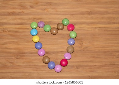 smarties heart on wooden surface