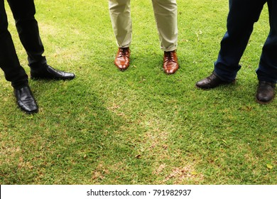 Smartly dressed businessmen standing on green grass in a park. This image can also be used to represent site meetings.