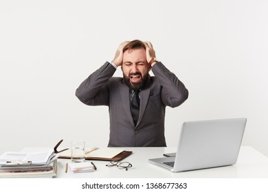 Smartly dressed office worker sitting at table grasping his head,nervous being in a difficult situation, has some work troubles, opened mouth screams from panic,closed his eyes in despair hopelessness