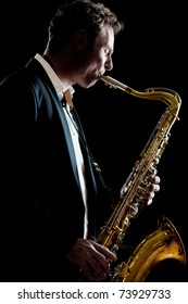 A smartly dressed saxophone player in a dark club setting