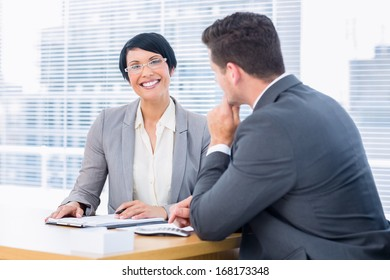 Smartly dressed young man and happy woman in a business meeting at office desk