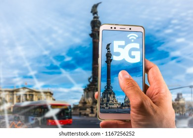 Smartphone with 5G on screen and FamousColumbus Monument, Colon, in Barcelona.High speed mobile technology in Barcelona and Spain or 5G for Europe Action Plan,5G deployment across all EU Member states