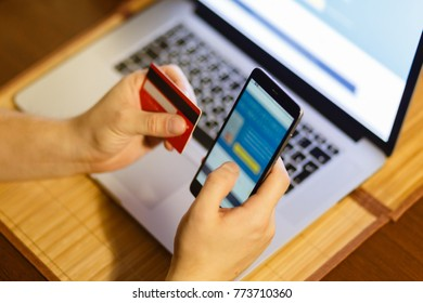 the smartphone app from the Bank for a report and credit card and wallet the background of the laptop. Man considers expenditures on a cash receipt. Mobile banking concept on screen.