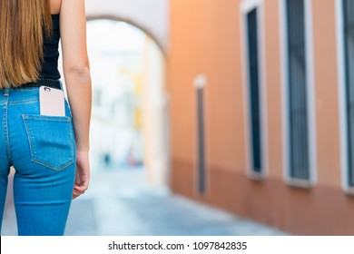Smartphone in the back pocket of jeans. A girl in jeans with a phone in the street. Copy space for text