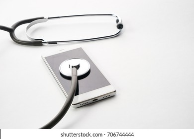 Smartphone being diagnosed with a stethoscope isolated on white background with copy space. Phone repair and service concept