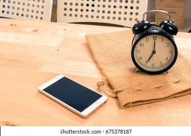 smartphone and black vintage retro alarm clock times at 7 o'clock morning on wooden desk in room, selective focus, copy space, vintage color tone, technology and working morning time concept