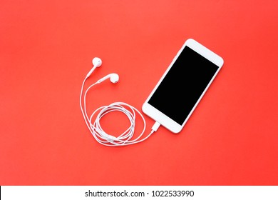 Smartphone with Blank Screen Connects to Earphones with Spiral Cable on Red Background Top View